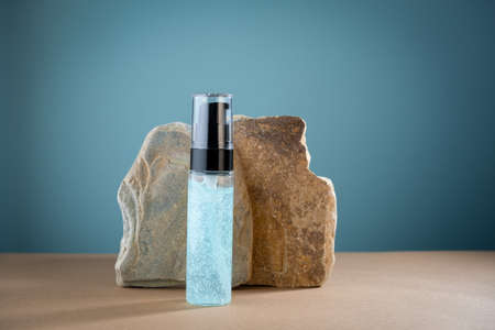 Mock up packaging of hyaluronic acid transparent jar on a blue background with stones. Natural cosmetics concept