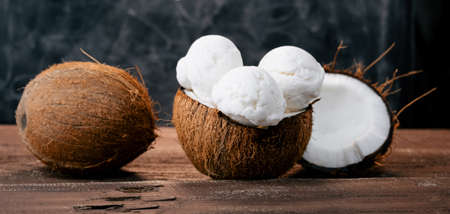 Fresh sweet coconut ice cream in a coconut shell on a wooden table. Sweet summer food.Wide banner. Stock fotó