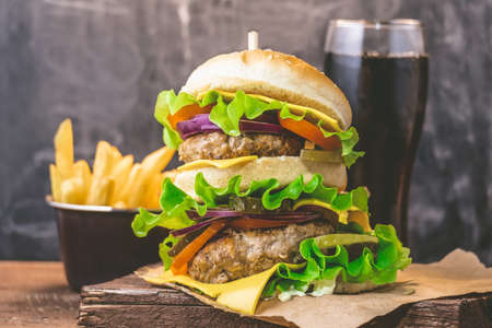 Big burger with meat cutlet and fresh drink on a wooden background. Junk food concept.