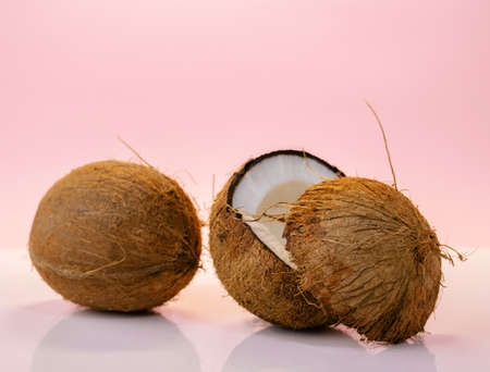 Coconut halves on a pastel pink background. Summer tropical food poster.