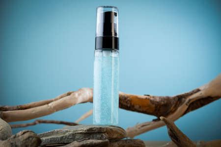 Mock up packaging of hyaluronic acid transparent jar on a blue background with twigs and stones. Natural cosmetics concept.