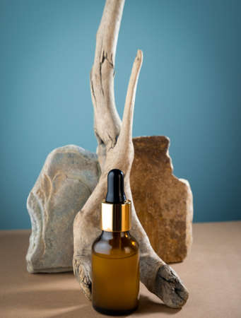Beauty care dropper brown glass bottle with wooden and stone decorations on a blue and brown background. Skin care concept.