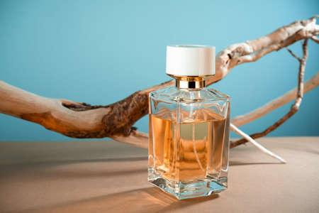Transparent mock up glass perfume bottle on blue beige background. Summer perfume concept.