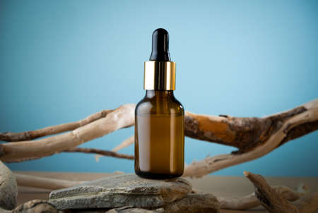 Beauty care dropper brown glass bottle with wooden and stone decorations on a blue and brown background. Skin care concept advertisment mock up.