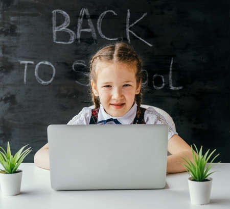 Cute little school girl sitting at the desk and using computer. Back to school and online lessons concept. Stock fotó