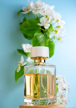 Packaging transparent glass expensive fresh fragrance perfume bottle on the background of blooming apple tree. Perfume poster on blue.