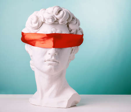 Plaster head with eyes covered red satin ribbon on blue background. Avoid problems concept. Stock fotó