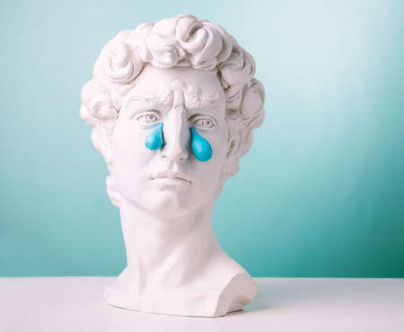 Plaster statue head with big blue tears on blue background. Creative depression concept. Stock fotó