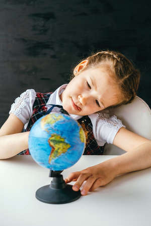 Little schoolgirl studies a globe at her desk against the background of a chalkboard.