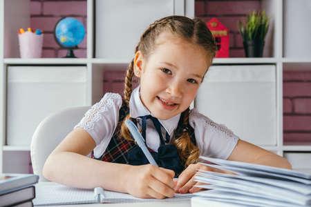Portrait beautiful positive little schoolgirl sitting at her desk and doing her homework. Back to school concept.