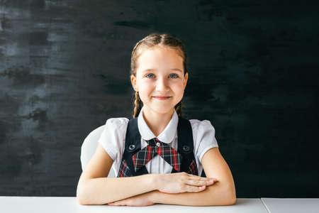 Portrait beautiful positive little schoolgirl sitting at her desk. Back to school concept. Stock fotó