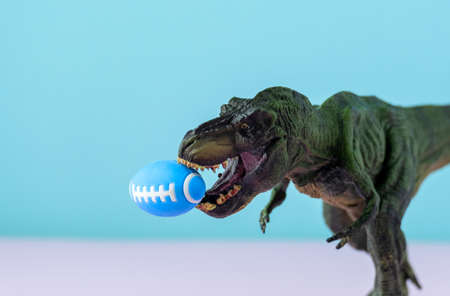 Big green dinosaur holding amirican football ball in mouth. Pastel background. Funny sports concept. Stock fotó
