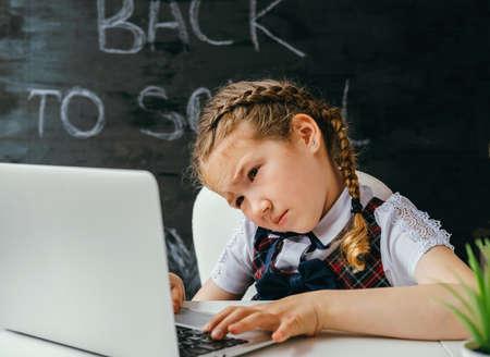 Little caucasian school girl using laprtop on a background of chalkboard with inscription back to school. Stock fotó