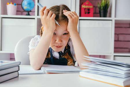 Tired sad schoolgirl girl sits at her homework
