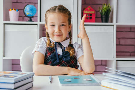 Beautiful little school girl in class is sitting at table with raised hand Stock fotó