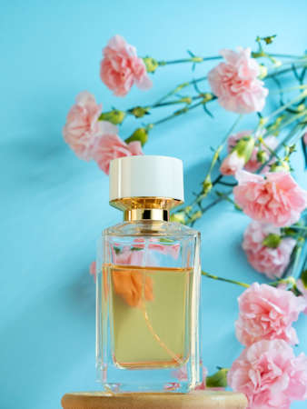 Packaging transparent glass expensive spicy fragrance perfume bottle on the background of pink carnation flowers. Perfume advertisment poster on blue. Stock fotó