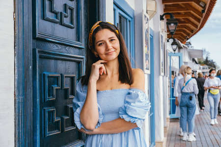 Young beautiful brunette in headscarf and blue dress agains ancient building with beautiful ancient door. Travel concept lifestyle portrait.