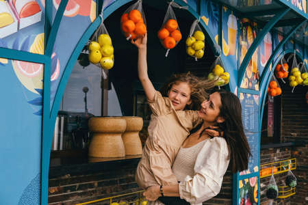 Beautiful young mother holds her daughter in her arms and they choose fruit in a fruit shop at a street market