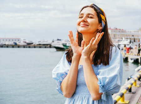 Pretty young woman lifestyle portrait on a background of blue sea. Summer travel concept.