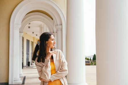 Portrait beautiful young woman weaing casual velvet jacket standing near column. Lifestyle mochrome portrait. Stock fotó