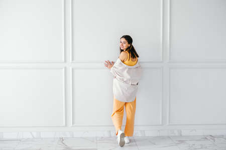 Beautiful young brunette shows off summer outfit corduroy shirt and cotton suit with sneakers on beige wall