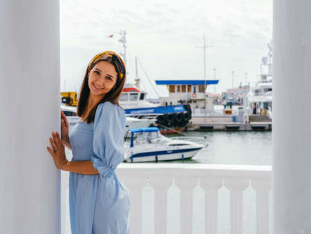 Portrait of young beautiful woman in blue dress on the shore against the background of yachts. Sea voyage concept.