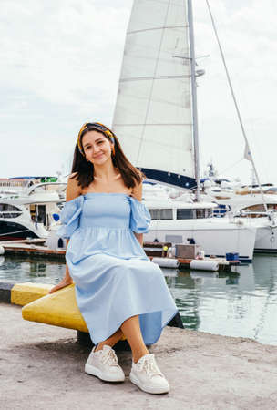Portrait of young beautiful woman in blue dress sitting on the shore against the background of yachts. Sea voyage concept.