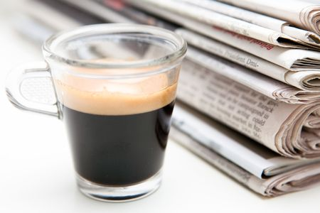 stack of newspapers with cup of espresso photo