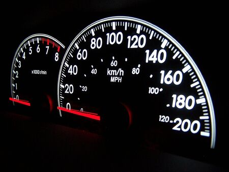 beside: Digital speedometer glowing in the dark with tachometer beside Stock Photo