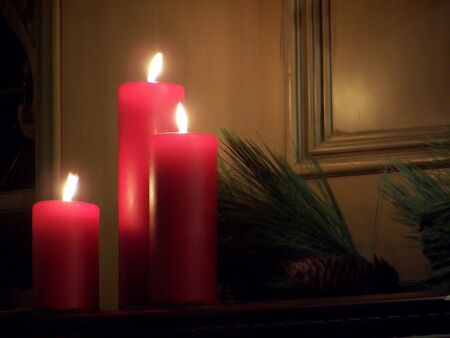 Red Candles on mantle with pine boughs and cone