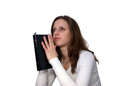 Isolation of a Young Woman holding a Bible in a praying posture