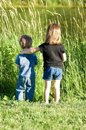 Two children overlooking a pond