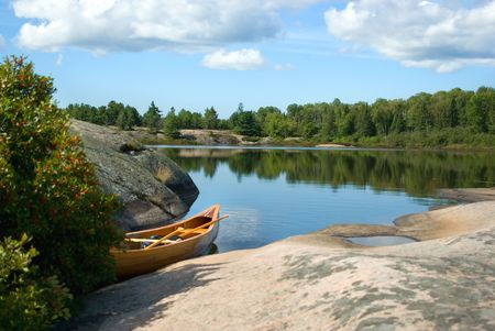 Cedar strip canoe sitting in water next to rocky shoreline photo