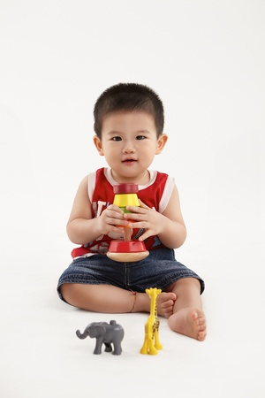 A young kid is happily playing with his colorful blocks and toys photo