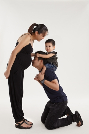 An expecting mother playing with her son carried by father photo