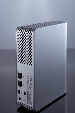 Back of a grey color external hard drive with grey background  Reflection on the bottom  photo