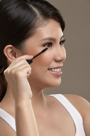 eye lashes: A female asian with natural make up holding a mascara pen applying mascara to her eye lashes