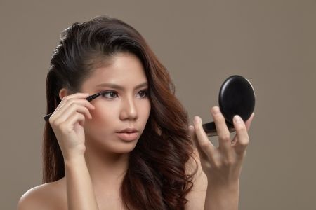 eye liner: A female asian with make up and pink eye shadow holding a liquid eye liner pen applying eye liner while looking at a mirror Stock Photo