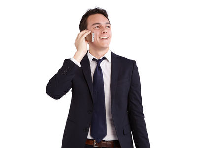 looking away from camera: A young caucasian male businessman smiling holding a mobile phone looking away from camera. Stock Photo