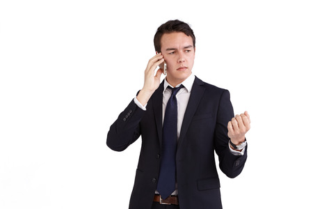 looking away from camera: A young caucasian male businessman frowns with raised hand while holding a mobile phone looking away from camera. Stock Photo