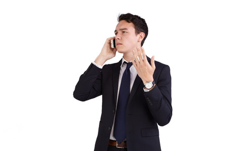 frowns: A young caucasian male businessman frowns with raised hand while holding a mobile phone looking away from camera. Stock Photo
