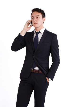 looking away from camera: Young caucasian male businessman looking unhappy holding a mobile phone looking away from camera.