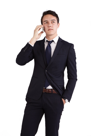 looking away from camera: A young caucasian male businessman looking unhappy holding a mobile phone looking away from camera.