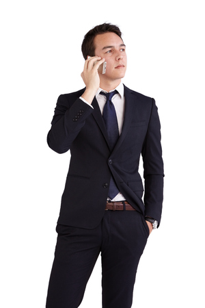 looking away from camera: A young caucasian male businessman looking thoughtful holding a mobile phone looking away from camera. Stock Photo