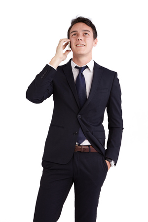 looking away from camera: A young caucasian male businessman looking happy holding a mobile phone looking away from camera.