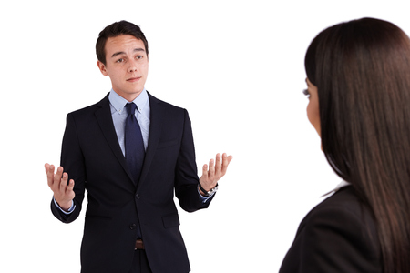 raised eyebrow: A young Caucasian business man is looking at a business woman. His eyebrow is raised and looking doubtful. Stock Photo