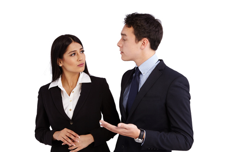 A young Caucasian business man is talking to a business woman disapprovingly. She is frowning while looking at him.