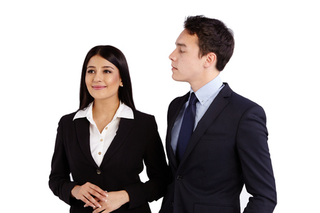 ignorant: A young Caucasian business man is looking at a business woman disapprovingly. Business woman is ignorant and smiling.