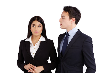 ignorant: A young Caucasian business man is looking at a business woman disapprovingly. Business woman is ignorant and not making eye contact. Stock Photo