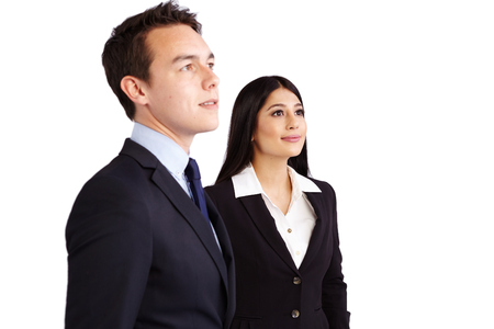 A young business man and business woman standing together looking at a distance. They are smiling.
